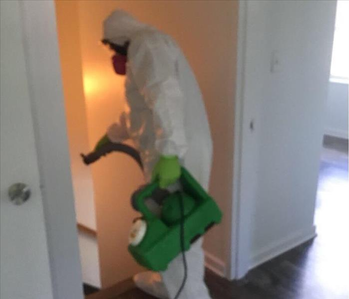 SERVPRO employee in PPE using a machine to fog down a staircase