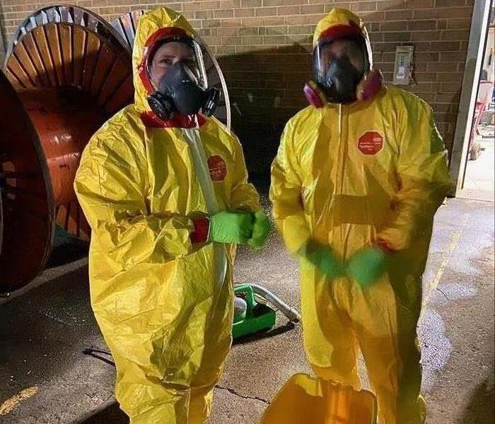 Two people wearing yellow Tyvek suits in a warehouse