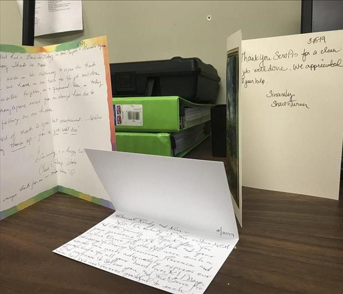 Three thank you cards propped open on a wooden desk