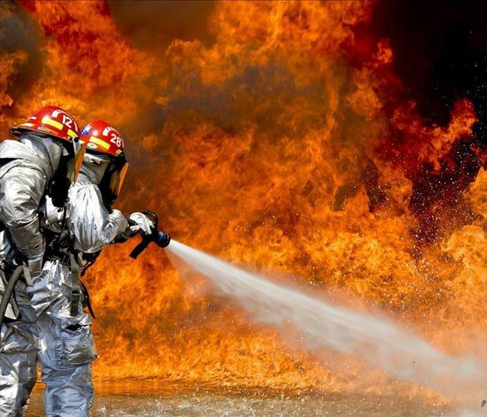 Two firefighters use a hose to put out large fire